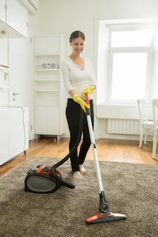 Bonne femme souriante nettoyant le tapis