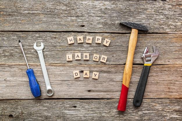 Bonne fête du travail sur des blocs de bois et des outils de construction sur la vue de dessus de fond en bois