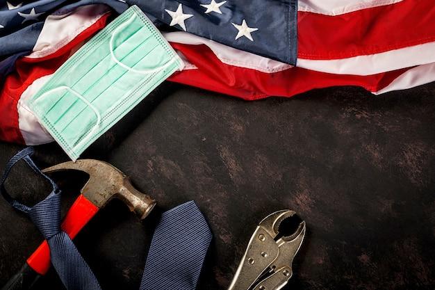 Bonne fête du travail ingénieur constructeur outils de travail masque médical protecteur et drapeau américain