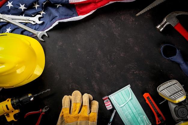 Bonne fête du travail plusieurs ingénieurs constructeur outils masque médical protecteur et drapeau américain