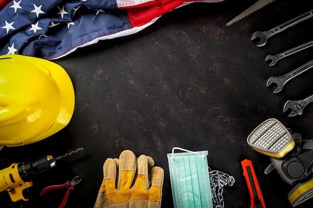 Bonne fête du travail plusieurs outils de travail de constructeur d'ingénieurs masque médical et drapeau américain