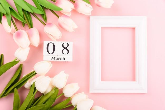 Bonne fête des femmes, fête des mères. vue de dessus plat poser fleur de tulipe et cadre photo sur rose