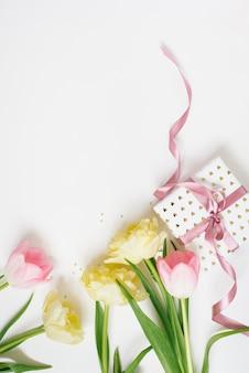 Bonne fête des mères, fête de la femme ou concept de voeux pour la saint-valentin. fond de couleurs pastel avec des fleurs de tulipes et une boîte-cadeau, mise à plat avec espace de copie.