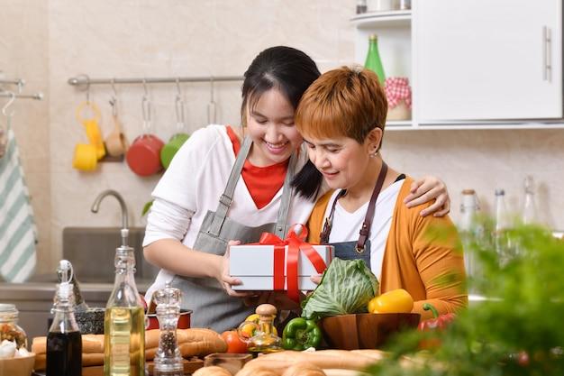 Bonne fête des mères! fille adolescente félicite la mère et donne un cadeau dans la cuisine à la maison