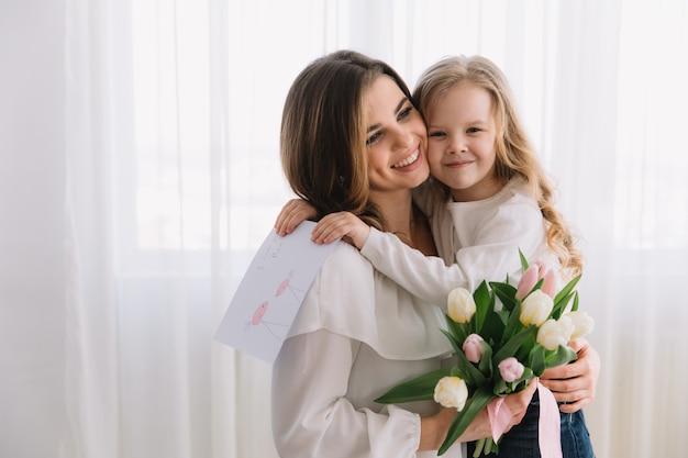 Bonne fête des mères. fille enfant félicite les mamans et lui donne une carte postale et des fleurs de tulipes.