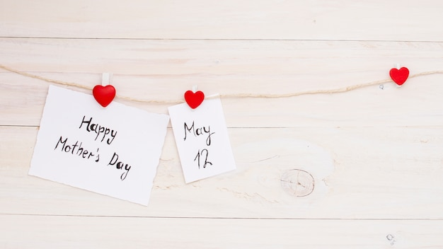 Bonne fête des mères et inscriptions du 12 mai épinglées à la corde