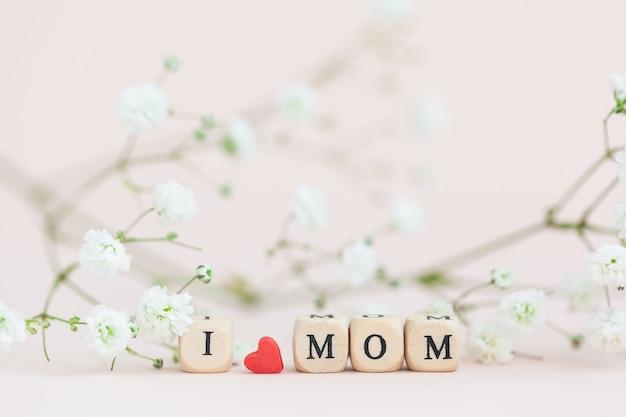 Bonne fête des mères. texte j'aime maman sur fond rose avec des fleurs de gypsophile floues. carte de voeux pour le concept de vacances.