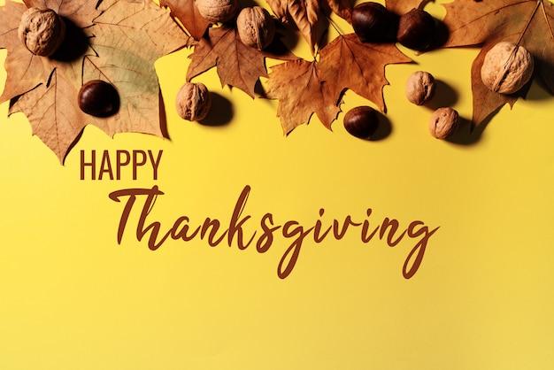 Bonne fête de thanksgiving avec des feuilles d'érable et des noix