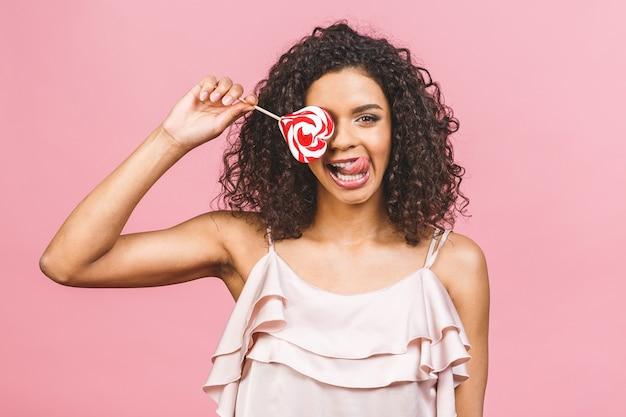 Bonne fille afro américaine sexy mangeant une sucette. beauté modèle glamour femme tenant des bonbons sucette colorée douce rose, isolé sur fond rose. bonbons.
