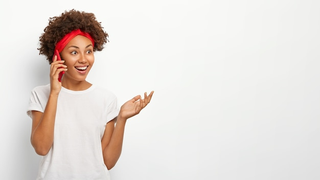 Bonne fille aux cheveux bouclés bénéficie d'une conversation téléphonique agréable, des gestes avec la paume, utilise un téléphone mobile, regarde de côté avec une expression heureuse