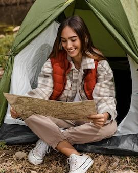 Bonne fille de camping dans la forêt en vérifiant la carte et les sourires