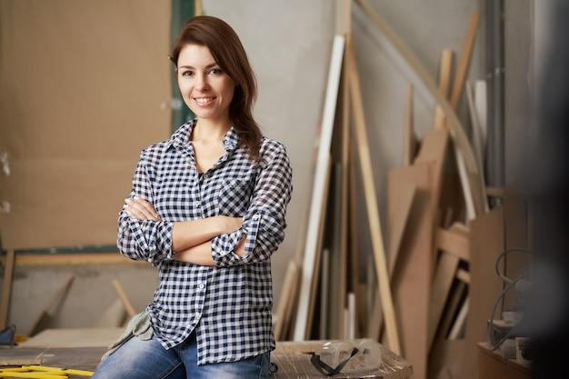 Bonne fille charpentier en chemise à carreaux avec les bras croisés en atelier