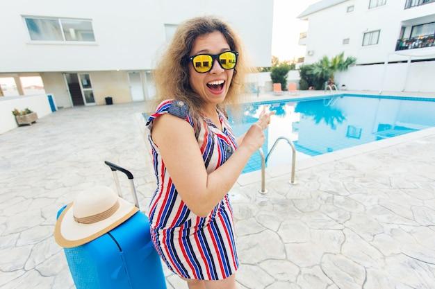 Bonne fille drôle en vacances d'été contre piscine, robe rayée habillée et lunettes de soleil