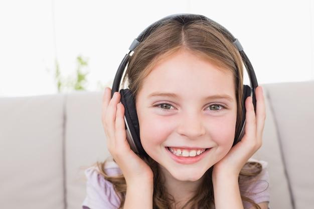 Bonne fille écoute de la musique à travers des écouteurs