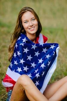 Bonne fille est assise sur l'herbe avec le drapeau américain