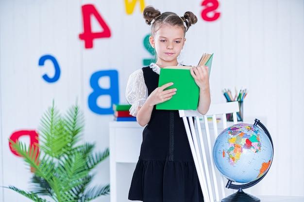 Bonne fille intelligente à l'école unifrom tenir le livre et regarder la caméra.