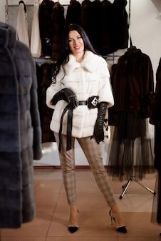 Bonne fille joyeuse posant en manteau de vison blanc dans un magasin de fourrure