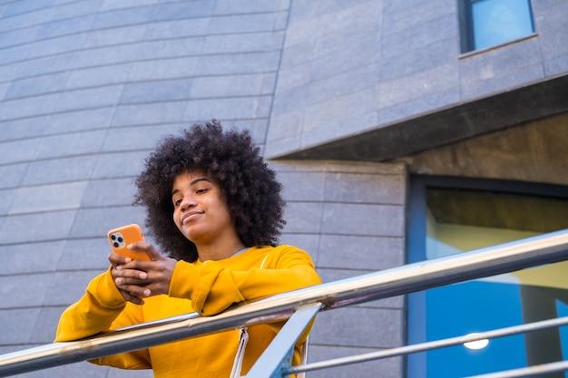 Bonne fille métisse millénaire dans la rue de la ville. jeune femme afro-américaine positive surfant sur le web, recherchant des informations, faisant des achats dans une boutique en ligne à l'extérieur