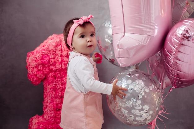 Bonne fille mignonne appréciant la fête d'anniversaire en se tenant près du décor et des ballons colorés. premier concept de fête d'anniversaire
