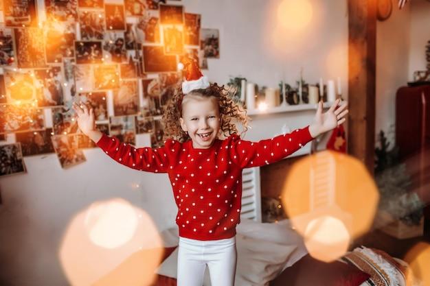 Bonne fille mignonne avec des boucles dans une atmosphère de nouvel an