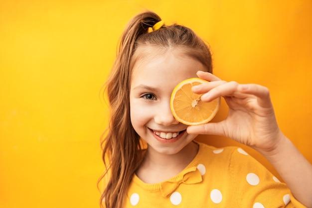 Bonne fille mignonne avec une peau parfaite propre cachant les yeux derrière une tranche de citron sur fond jaune