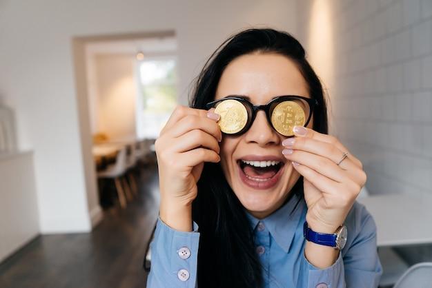 Bonne fille qui rit tenant des bitcoins dorés par les yeux
