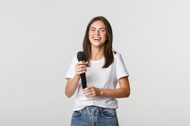 Bonne fille en riant tenant le microphone et chantant le karaoké, blanc.