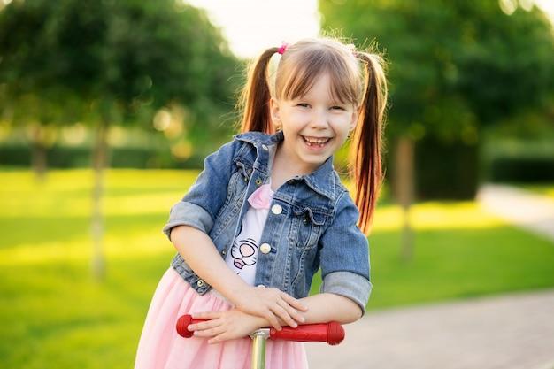 Bonne fille souriante de six ans dans le parc d'été