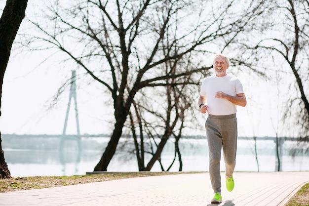 Bonne forme. jolly homme mûr qui court dans le parc tout en se reposant