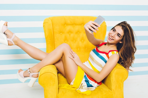 Bonne heure d'été de joyeuse femme ypung élégante en robe colorée, avec de longs cheveux bouclés brune faisant selfie dans une chaise jaune sur un mur rayé. s'amuser, exprimer des émotions positives.