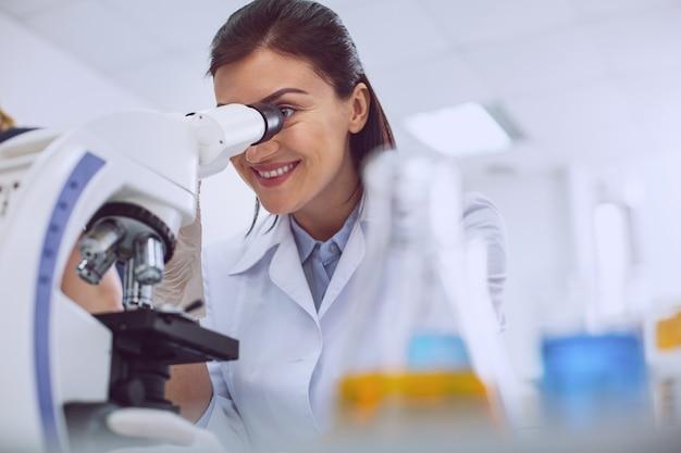 Bonne humeur. alerte biologiste professionnel portant un uniforme et regardant dans le microscope