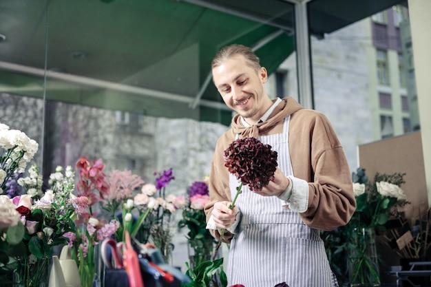 Bonne humeur. enthousiaste jeune homme gardant le sourire sur son visage tout en regardant la fleur