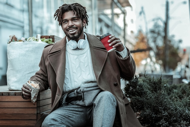 Bonne humeur. heureux homme gardant le sourire sur son visage tout en tenant une tasse de papier dans la main gauche