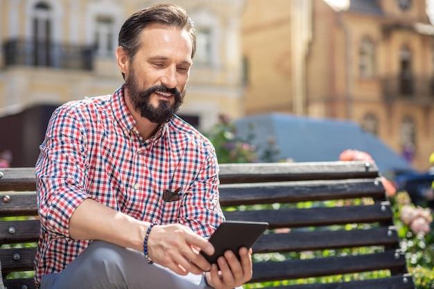 De bonne humeur. homme adulte joyeux à l'aide de son livre électronique alors qu'il était assis sur le banc