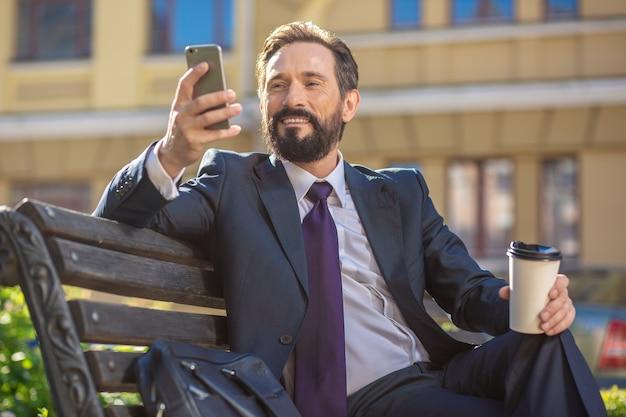 De bonne humeur. homme d'affaires barbu souriant assis sur le banc tout en se reposant avec une tasse de café