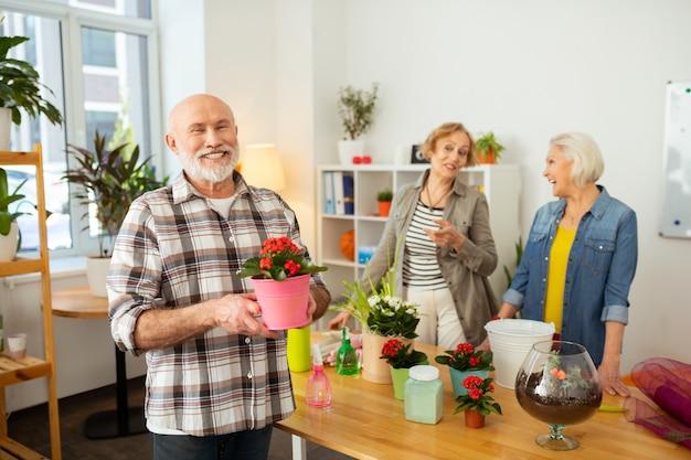 Bonne humeur. un homme âgé joyeux qui vous sourit tout en tenant un pot de fleurs dans ses mains