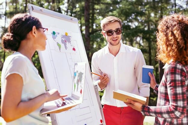 Bonne humeur. homme élégant inspiré debout près du tableau et discutant de son projet avec ses amis