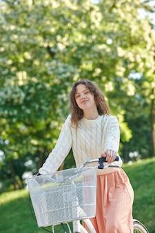 Bonne humeur. une jolie fgirl sur un vélo se sentant bien et souriante