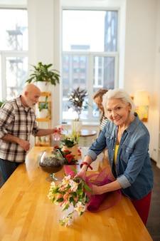 Bonne humeur. vue de dessus d'une femme âgée positive souriant tout en faisant son activité préférée
