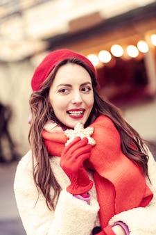 Bonne idée. charmante femme gardant le sourire sur son visage tout en tenant le cookie dans la main droite