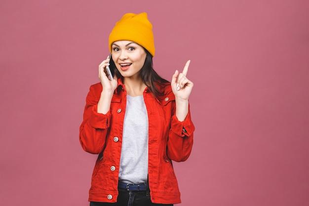 Bonne idée! portrait d'une femme étonnée heureuse dans des vêtements lumineux, parler au téléphone isolé sur le mur rose.