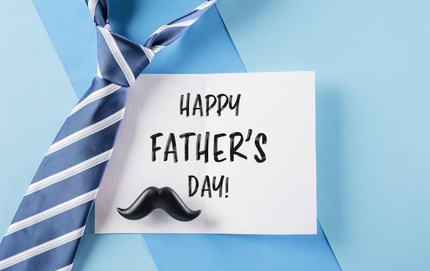 Bonne inscription pour la fête des pères dans une carte célèbre et une cravate à carreaux sur fond bleu pastel