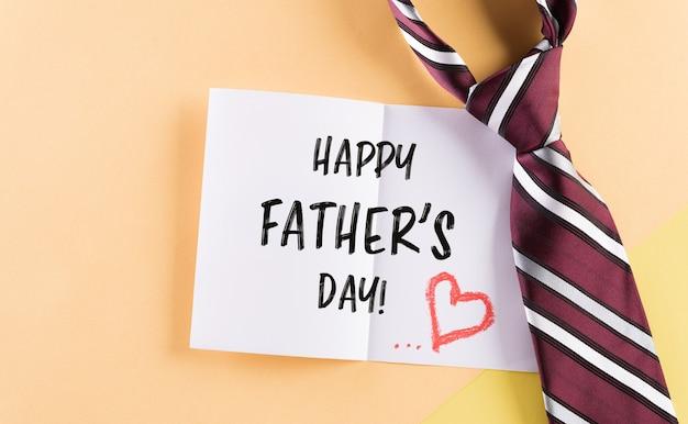 Bonne inscription pour la fête des pères dans une carte célèbre et une cravate à carreaux sur fond pastel