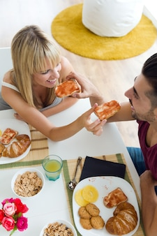 Bonne jeune couple qui profite du petit-déjeuner dans la cuisine.
