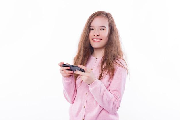 Bonne jeune écolière jouant au smartphone sur blanc