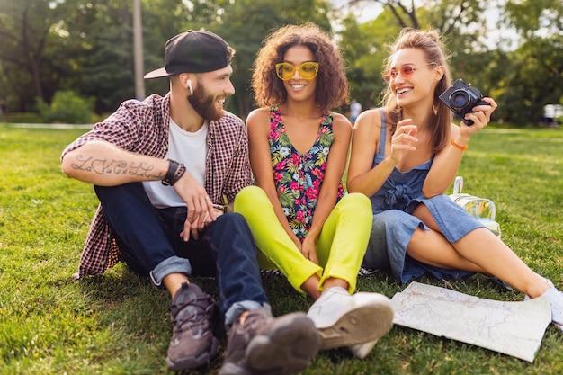 Bonne jeune entreprise d'amis assis dans le parc, l'homme et la femme s'amusant ensemble, style de mode hipster d'été coloré, voyageant avec appareil photo, parlant, souriant
