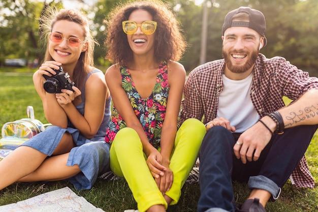 Bonne jeune entreprise d'amis assis parc, homme et femme s'amusant ensemble, voyageant avec appareil photo,
