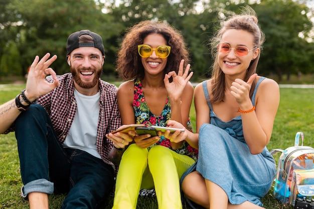 Bonne jeune entreprise d'amis souriants assis dans le parc à l'aide de smartphones, s'amuser ensemble