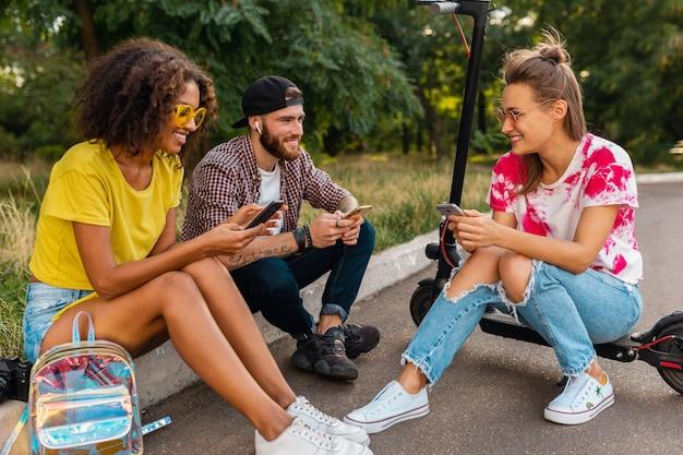 Bonne jeune entreprise d'amis souriants assis dans le parc sur l'herbe avec scooter électrique, homme et femme s'amusant ensemble