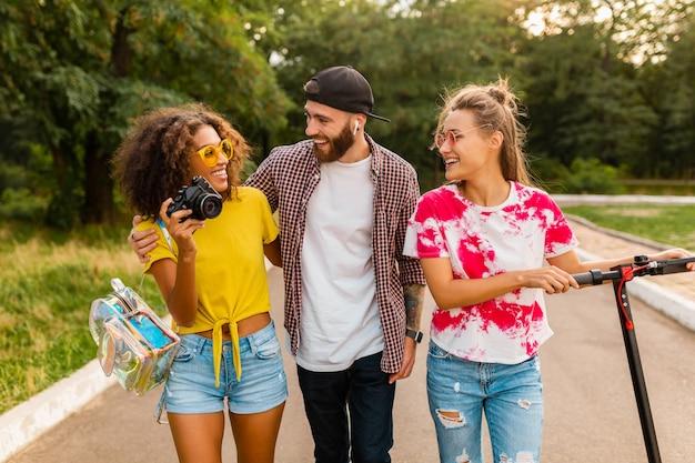Bonne jeune entreprise d'amis souriants marchant dans le parc avec scooter électrique, homme et femme s'amusant ensemble